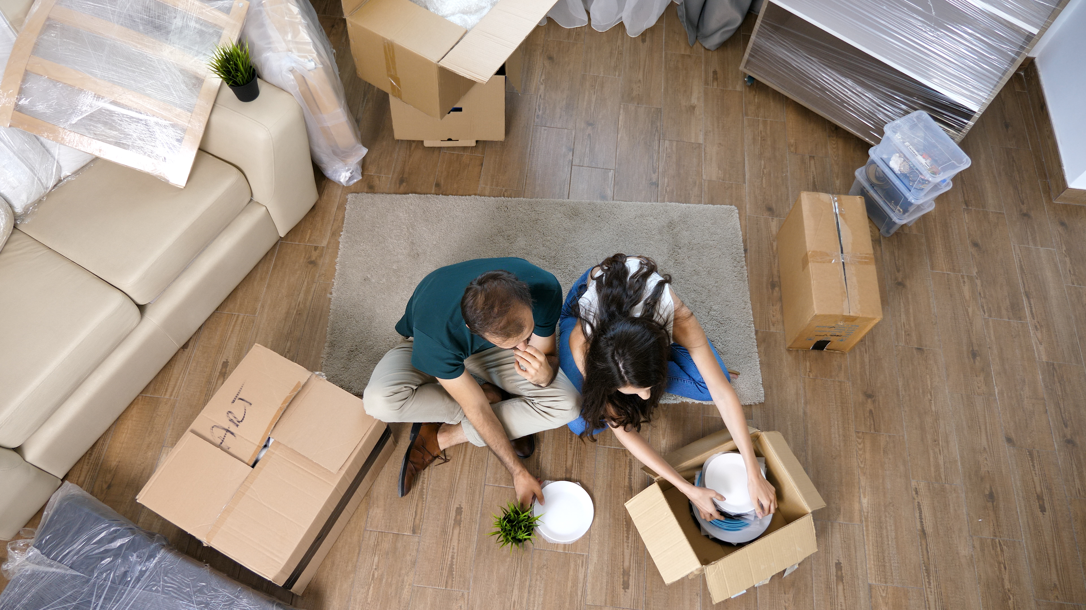 young-couple-moving-in-new-home-and-unpacking-carb-VA5HRWJ